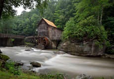 Babcock State Park, West Virginia. Glade Creek, swollen from heavy rains, dishes by in the foreground as an Old Grist Mill sits in the background in Babcock stock photography