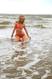 Babe on the beach. Female model in the sea on her knees wearing her bikini Stock Photos