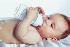 Babe with blue eyes is holding a bottle Royalty Free Stock Photos