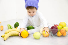 The babe in an environment of the fresh vegetables, isolated on the white Royalty Free Stock Photo