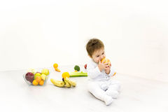 The babe in an environment of the fresh vegetables,  on the white Royalty Free Stock Images