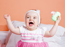 Babe girl playing laughing toy. Stock Images