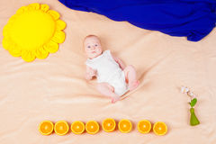 Babe lies on the background of the composition. Babe with oranges in a painting from the fabric Stock Image