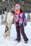 Babe med snowboarden i snön royaltyfri fotografi