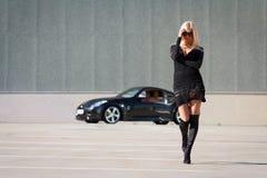 Babe near super car. Glamorous blond babe near tuned supercar stock image