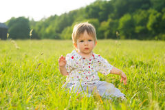 Babe sit on the grass. Little boy playing on the lawn Stock Photography