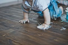 The child eats the cake hands sitting on the floor 5605. royalty free stock photography