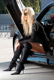Babe sitting in a car. Glamorous blond babe sitting in a tuned black sportcar stock photography