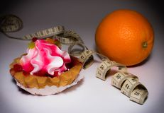 Babeczka, centymetr, pomarańcze na lekkim tle, cukierki i owoc dla diety, Obrazy Royalty Free