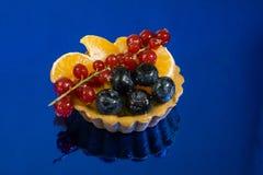 Babeczka z świeżą życiorys owoc, pomarańcze, czarna jagoda, czerwony rodzynek, bocznego widoku fotografia, lustrzany błękitny tło obrazy royalty free