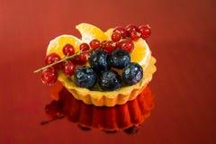 Babeczka z świeżą życiorys owoc, pomarańcze, czarna jagoda, czerwony rodzynek, bocznego widoku fotografia, lustrzany czerwony tło zdjęcia stock