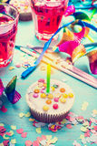 Babeczka z świeczką nad partyjnym wystroju tłem urodzinowej karty powitanie szczęśliwy Obrazy Stock