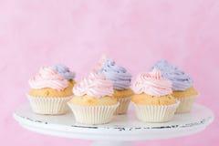 Babeczki dekorować z fiołka i menchii buttercream na podławym shic stojaku na pastelowych menchii tle Zdjęcie Royalty Free