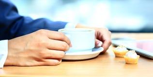 Babeczki i filiżanka kawy przy ranku biznesem Fotografia Stock