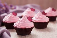 Babeczki tradycyjnego świętowania słodki deser z różowymi kremowymi i czerwonymi sercami w rzędzie na rocznika tle Obrazy Royalty Free