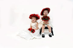 Babes and Roses. Two sisters in wedding as flower girls,  sit in an all white room holding red roses.  Both are wearing off white lace dresses and red straw hats Stock Photography