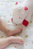 Babie's feet with her doll. On white bed Royalty Free Stock Images