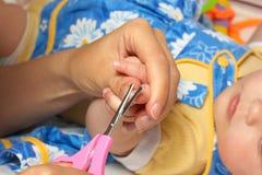 babiecuttingfingret spikar s Arkivfoton