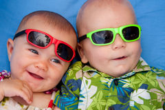 Babies. Two babies on holidays in the tropics, wearing sunglasses and smiling (five and three months old