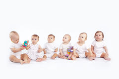 Babies. Group of babies sitting on white studio background Royalty Free Stock Photo