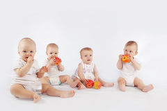 Babies. Group of babies with apples sitting on white studio background Royalty Free Stock Photo