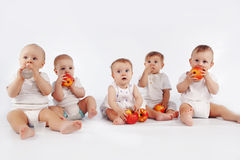 Babies. Group of babies with apples sitting on white studio background Stock Photography