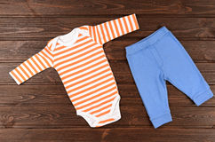 Babies bodysuits and pants on wooden background Royalty Free Stock Photo