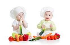 Babies boy and girl with healthy food vegetables royalty free stock photos