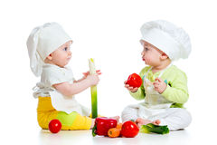 Babies boy and girl with vegetables. Babies boy and girl wearing a chef hat with healthy  food vegetables Royalty Free Stock Photos
