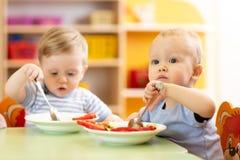 Babies children eating healthy food in nursery or kindergarten. Babies children boys eating healthy food in nursery or kindergarten stock photos