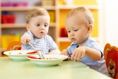 Babies children eating healthy food in nursery or kindergarten. Babies children boys eating healthy food in nursery or kindergarten royalty free stock images