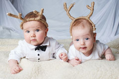 Babies with deer horns on bright background Royalty Free Stock Photography