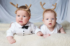 Babies with deer horns on bright background Royalty Free Stock Photos