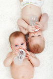 Babies drinking water from feeding bottles Stock Photos