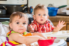 Babies Eat Breakfast. Two cute babies are eating breakfast together royalty free stock images