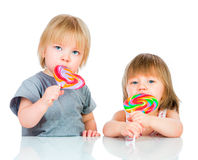 Babies eating a sticky lollipop. On white background stock image