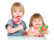 Babies eating a sticky lollipop Royalty Free Stock Image