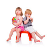 Babies eating a sticky lollipop Royalty Free Stock Photography