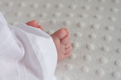 Babies feet sticking out of a baptism outfit Royalty Free Stock Photography