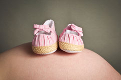 Babies first shoes on a pregnant womans bump Stock Photos