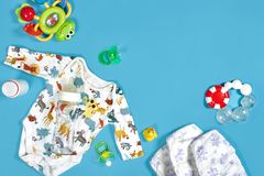 Babies goods: cloth diaper, baby powder, nibbler, cream, teether, soother, baby toy on blue background. Copy space. Top. View. Early childhood development royalty free stock photos