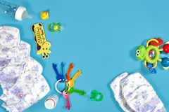 Babies goods: cloth diaper, baby powder, nibbler, cream, teether, soother, baby toy on blue background. Copy space. Top. View. Early childhood development stock image