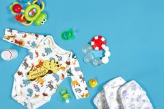 Babies goods: cloth diaper, baby powder, nibbler, cream, teether, soother, baby toy on blue background. Copy space. Top. View. Early childhood development stock images