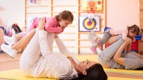 Babies have a fun while mothers doing workout in gym class to loose extra weight. Child-friendly fitness for women with. Babies have fun pastime while mothers stock images