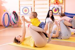 Babies have a fun while mothers doing workout in gym class to loose extra weight. Child-friendly fitness for women with. Babies have fun pastime while mothers stock photo