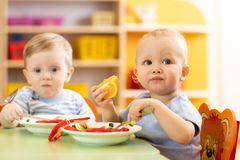 Babies have a lunch in nursery royalty free stock photo