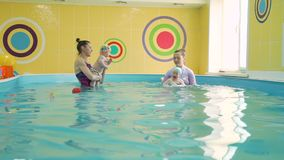 Babies with instructors at infant swimming class. Cute babies with instructors at infant swimming class. Swimming instructors teaching babies to swim in the stock video footage
