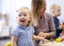Babies in kindergarten. Kids toddlers in nursery school. Little children preschoolers play with teacher. royalty free stock photography