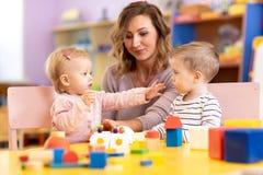 Babies in kindergarten. Kids toddlers in nursery school. Little girl and boy preschoolers playing with teacher. stock photos