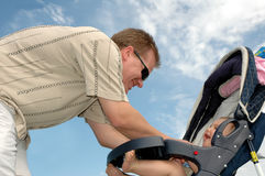 Babies Laugh. Man bends over baby and makes him laugh. Blue sky behind. Baby in stroller Stock Image